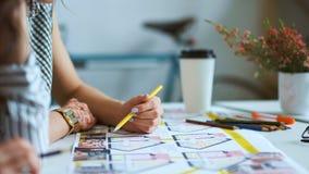 Κλείστε επάνω δύο αρχιτεκτόνων γυναικών που συζητούν το σχέδιο μαζί στο γραφείο με τα σχεδιαγράμματα φιλμ μικρού μήκους