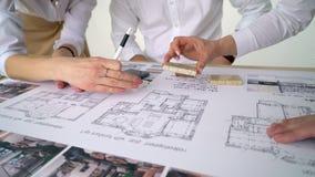 Κλείστε επάνω δύο αρχιτεκτόνων που συζητούν το σχέδιο μαζί στο γραφείο με τα σχεδιαγράμματα φιλμ μικρού μήκους