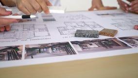 Κλείστε επάνω δύο αρχιτεκτόνων που συζητούν το σχέδιο μαζί στο γραφείο με τα σχεδιαγράμματα απόθεμα βίντεο