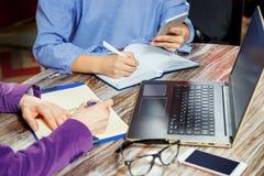 Κλείστε επάνω δύο γυναικών που κάνουν τα αρχεία σε μια συνεδρίαση σημειωματάριων σε ένα lap-top Δύο ζευγάρια των γυναικών ` s παρ Στοκ φωτογραφίες με δικαίωμα ελεύθερης χρήσης