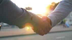 Κλείστε επάνω δύο επιτυχών επιχειρηματιών που χαιρετούν ο ένας τον άλλον στα πλαίσια της στάθμευσης αυτοκινήτων νεολαίες συναδέλφ απόθεμα βίντεο