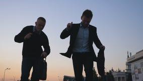 Κλείστε επάνω δύο ευτυχών νέων επιχειρηματιών με τον αστείο χορό χαρτοφυλάκων περπατώντας μετά από την επιτυχή επιχειρησιακή διαπ απόθεμα βίντεο