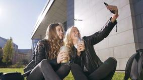 Κλείστε επάνω δύο καυκάσιων ευτυχών κοριτσιών που παίρνουν selfie τη φωτογραφία στο smartphone περπατώντας στο πάρκο στο κέντρο τ φιλμ μικρού μήκους
