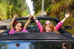 Κλείστε επάνω δύο μικρών όμορφων κοριτσιών που κάθονται σε ένα αυτοκίνητο πολυτέλειας που φορά ένα ροζ ντύνει, απολαμβάνοντας την στοκ εικόνες
