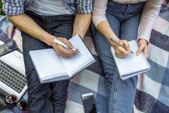 Κλείστε επάνω δύο σπουδαστές προετοιμάζεται για τη συνεδρίαση σεμιναρίου στη χλόη εκπαίδευση on-line Στοκ φωτογραφία με δικαίωμα ελεύθερης χρήσης