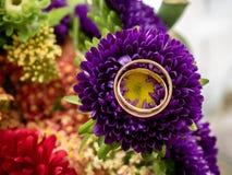 Κλείστε επάνω δύο χρυσών δαχτυλιδιών της νύφης και του νεόνυμφου πάνω από ένα λουλούδι μιας ζωηρόχρωμης ανθοδέσμης των λουλουδιών στοκ φωτογραφία με δικαίωμα ελεύθερης χρήσης