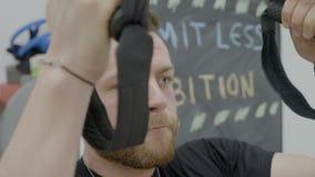 Κλείστε επάνω ελκυστικός επαγγελματικός gymnast που ιδρώνει και που τινάζει επιλύοντας έντονα τα όπλα μυών του στα ελαστικά δαχτυ απόθεμα βίντεο
