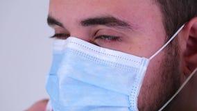 Κλείστε επάνω ενός αρσενικού προσώπου χειρούργων ` s που τίθεται σε μια χειρουργική μάσκα απόθεμα βίντεο