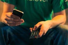 Κλείστε επάνω ενός ατόμου που κρατά ένα τηλέφωνο κυττάρων και μια TV τηλεχειρισμός Στοκ Φωτογραφία