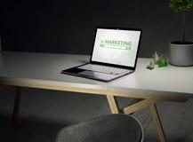 Κλείστε επάνω ενός γραφείου με ένα lap-top και του ε-μάρκετινγκ στην οθόνη και προεδρεύστε σε ένα εκλεκτής ποιότητας άσπρο ξύλινο ελεύθερη απεικόνιση δικαιώματος