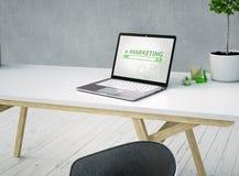 Κλείστε επάνω ενός γραφείου με ένα lap-top και του ε-μάρκετινγκ στην οθόνη και προεδρεύστε σε ένα εκλεκτής ποιότητας άσπρο ξύλινο απεικόνιση αποθεμάτων