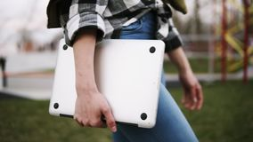 Κλείστε επάνω ενός κομψού κοριτσιού στους περιπάτους τζιν μέσω του πάρκου με ένα lap-top στο χέρι της Βέβαιος περίπατος Πλάγια όψ απόθεμα βίντεο