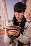 Κλείστε επάνω ενός λυπημένου άστεγου νεαρού άνδρα στις οδούς, με ένα καπέλο στα χέρια του, ζητώντας τα χρήματα, σε ένα θολωμένο υ Στοκ Φωτογραφίες