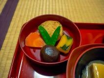 Κλείστε επάνω ενός μεσημεριανού γεύματος που εξυπηρετείται σε ένα κόκκινο καλύπτει, σε ένα εστιατόριο στην Ιαπωνία Στοκ Εικόνες