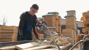 Κλείστε επάνω ενός νέου εργαζομένου ξυλουργών που φορά τα προστατευτικά δίοπτρα κατασκευής και την ομοιόμορφη χρησιμοποιώντας ξύλ απόθεμα βίντεο