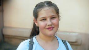 Κλείστε επάνω ενός νέου κοριτσιού που χαμογελά δεδομένου ότι εξετάζει τη κάμερα απόθεμα βίντεο