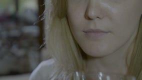 Κλείστε επάνω ενός ξανθού λεπτού θηλυκού που βάζει ένα άσπρο μικρό χάπι στη γλώσσα της και που καταπίνει το με ένα ποτήρι του νερ φιλμ μικρού μήκους