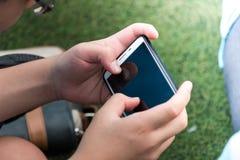 Κλείστε επάνω ενός παιδιού χρησιμοποιώντας το κινητό έξυπνο τηλέφωνο στοκ εικόνα