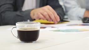 Κλείστε επάνω ενός φλιτζανιού του καφέ στον πίνακα businesspeople εργαζόμενος στο υπόβαθρο απόθεμα βίντεο