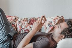 Κλείστε επάνω ενός χαλαρωμένου καυκάσιου ατόμου χρησιμοποιώντας το έξυπνο τηλέφωνο στον καναπέ στο καθιστικό στο σπίτι στοκ φωτογραφίες με δικαίωμα ελεύθερης χρήσης
