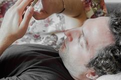 Κλείστε επάνω ενός χαλαρωμένου καυκάσιου ατόμου χρησιμοποιώντας το έξυπνο τηλέφωνο στον καναπέ στο καθιστικό στο σπίτι στοκ φωτογραφία με δικαίωμα ελεύθερης χρήσης