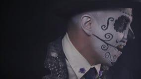 Κλείστε επάνω ενός χαμογελώντας ατόμου που χορεύει, ένα καπέλο και ένα πρόσωπο που χρωματίζονται που φορά ως κρανίο, 4k απόθεμα βίντεο