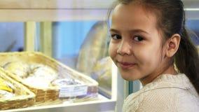 Κλείστε επάνω ενός χαριτωμένου μικρού κοριτσιού που χαμογελά στη κάμερα στο αρτοποιείο στοκ φωτογραφία με δικαίωμα ελεύθερης χρήσης