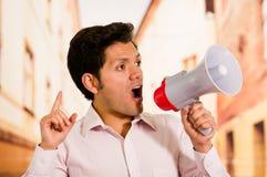Κλείστε επάνω ενός όμορφου ατόμου που κραυγάζει με megaphone, κάνοντας ένα σήμα με δικούς του παραδώστε ένα θολωμένο υπόβαθρο Στοκ εικόνες με δικαίωμα ελεύθερης χρήσης