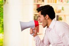 Κλείστε επάνω ενός όμορφου ατόμου που κραυγάζει με megaphone σε ένα θολωμένο υπόβαθρο Στοκ Εικόνες