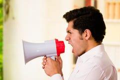 Κλείστε επάνω ενός όμορφου ατόμου που κραυγάζει με megaphone σε ένα θολωμένο υπόβαθρο Στοκ φωτογραφία με δικαίωμα ελεύθερης χρήσης