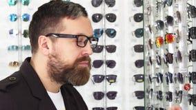 Κλείστε επάνω ενός ώριμου ατόμου που εξετάζει τα γυαλιά για την πώληση στην επίδειξη απόθεμα βίντεο