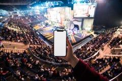 Κλείστε επάνω ενός smartphone εκμετάλλευσης γυναικών με την κενή οθόνη κινητή με θολωμένο το συναυλία υπόβαθρο στοκ εικόνες