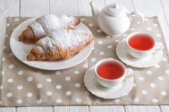 κλείστε επάνω Εορτασμός ημέρας βαλεντίνων ` s Ρομαντικό πρόγευμα για δύο Πρόσφατα ψημένα γαλλικά croissants και τσάι μούρων στα δ στοκ εικόνες