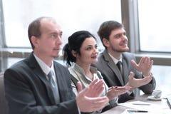 κλείστε επάνω επιχειρησιακή ομάδα που επιδοκιμάζει τον ομιλητή, που κάθεται στον εργασιακό χώρο στοκ φωτογραφίες με δικαίωμα ελεύθερης χρήσης