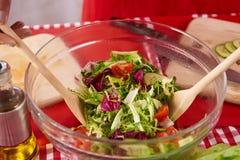 κλείστε επάνω Η νοικοκυρά ανακατώνει τη σαλάτα στην κουζίνα στοκ εικόνες