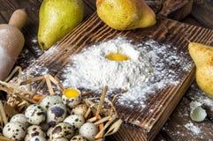 κλείστε επάνω Κίτρινος λέκιθος αυγών σε έναν λόφο του άσπρου αλευριού, που περιβάλλεται από τα ώριμα μεγάλα αχλάδια ζωή αγροτική  στοκ φωτογραφία