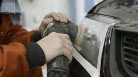 Κλείστε επάνω κεφάλι για των αυτόματων μηχανικών buffing και στίλβωσης αυτοκινήτων φως r Εργαζόμενος που γυαλίζει τον προβολέα εν στοκ φωτογραφίες