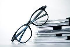 Κλείστε επάνω μαύρα eyeglasses ανάγνωσης στη συσσώρευση του γραφείου pape Στοκ εικόνα με δικαίωμα ελεύθερης χρήσης