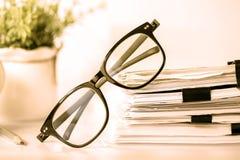 Κλείστε επάνω μαύρα eyeglasses ανάγνωσης στη συσσώρευση του εγγράφου γραφείων, Στοκ Φωτογραφία