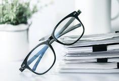 Κλείστε επάνω μαύρα eyeglasses ανάγνωσης στη συσσώρευση του εγγράφου γραφείων, Στοκ εικόνες με δικαίωμα ελεύθερης χρήσης