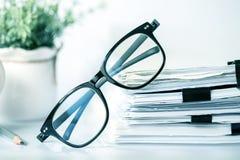 Κλείστε επάνω μαύρα eyeglasses ανάγνωσης στη συσσώρευση pap γραφείων Στοκ Φωτογραφία