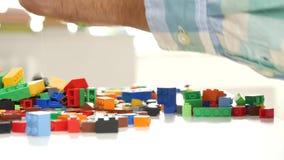 Κλείστε επάνω με τα χέρια Grandpa παίζοντας με το πλαστικό παιχνίδι παιδιών κατασκευής τούβλων απόθεμα βίντεο