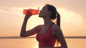 Κλείστε επάνω μιας αρκετά νέας κυρίας που ανοίγει ένα μπουκάλι και που πίνει από το φιλμ μικρού μήκους