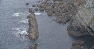 Κλείστε επάνω μιας βάσης απότομων βράχων με τη θάλασσα που χτυπά τους βράχους φιλμ μικρού μήκους
