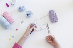 Κλείστε επάνω μιας γυναίκας που δημιουργεί με το χέρι μαλλιού - γίνοντα bootees για ένα β Στοκ φωτογραφίες με δικαίωμα ελεύθερης χρήσης