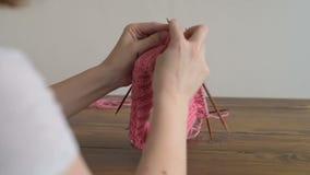 Κλείστε επάνω μιας γυναίκας που πλέκει ένα καπέλο φιλμ μικρού μήκους