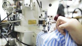 Κλείστε επάνω μιας γυναίκας που ράβει ένα μπλε και άσπρο πουκάμισο σε ένα εργοστάσιο απόθεμα βίντεο