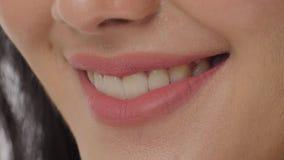 Κλείστε επάνω μιας γυναίκας που χαμογελά σε ένα άσπρο κλίμα φιλμ μικρού μήκους