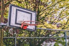Κλείστε επάνω μιας εγκαταλειμμένης στεφάνης καλαθοσφαίρισης χωρίς το καθαρό και οξυδωμένο πλαίσιο στοκ εικόνα