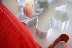 Κλείστε επάνω μιας κόκκινου πετσέτας, ενός λευκού, ενός ασημιού, και ενός κόκκινου κόπτη μπισκότων σε μια ελαφριά αντίθετη κορυφή στοκ εικόνες